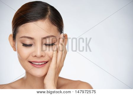 Asian woman with closed-eyes touching her face