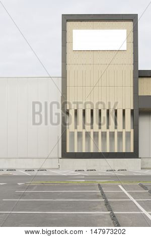 Mock up. Blank billboard with copy space for text message or content. Store or industrial building wall, near car parking.