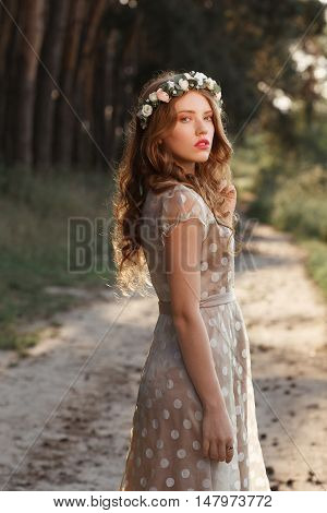 Beautiful girl walking in forest on sunset. Young woman in polka-dot gray dress strolling in nature, path between pine trees background, free space
