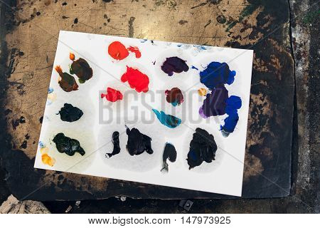 Paper palette with different color smears. Painters pallet with colorful variety of paints. Artist workshop, picture drawing concept