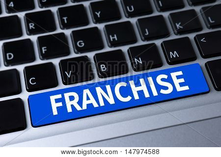 FRANCHISE a message on keyboard businessman work hard and use computer