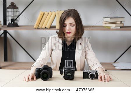 Different generation of camera comparison. Beautiful female blogger looking at three samples of photographer equipment. Technology progress concept