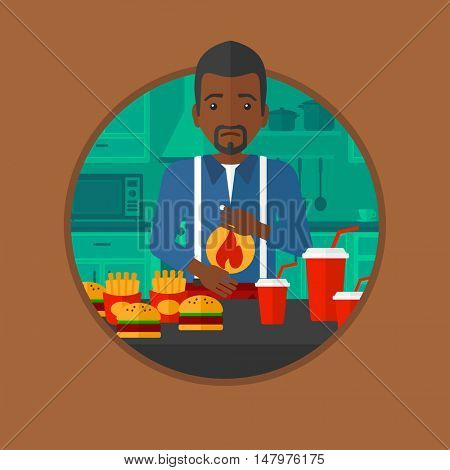 An african man suffering from heartburn. Man standing in the kitchen in front of table with junk food and suffering from heartburn. Vector flat design illustration in the circle isolated on background
