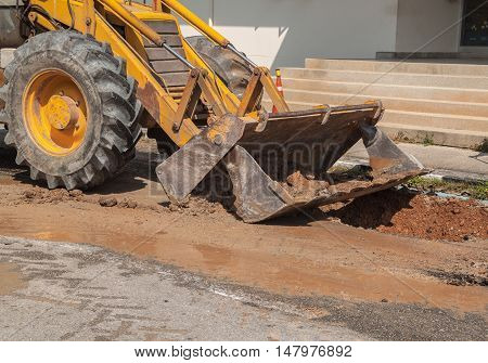 Excavator working on the Repair of pipe water and sewerage on a road Worker  to dig a hole to fix