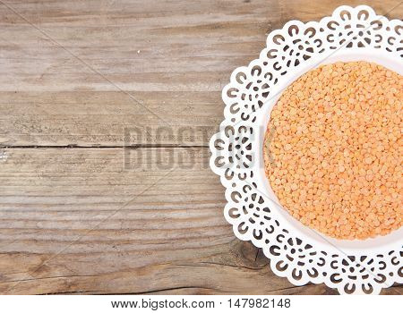 Red lentils on white plate with wooden background