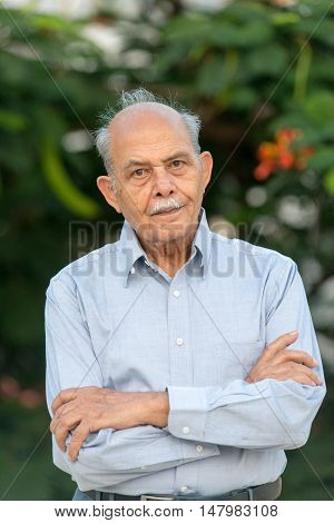 An outdoor photo of a senior Indian / South Asian man looking to camera - vertical composition