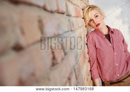 Young blonde woman daydreaming by brick wall.