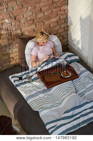 Young woman using tablet in bed, having breakfast. Above view.