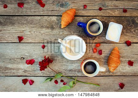 Two coffees, croissants, sugar, candy, yoghurt, rose and petals on old wooden background. Top view.