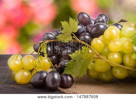 Blue and green grapes on wooden table with a blurred background.