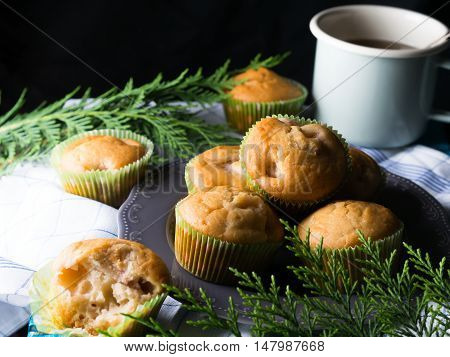 Vegan eggs free spelt wheat muffins with peaches and apples in green paper cases on checkered napkin