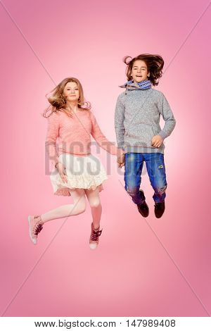 Two happy teenage boy and girl jumping together over pink background. Friendship. First love.