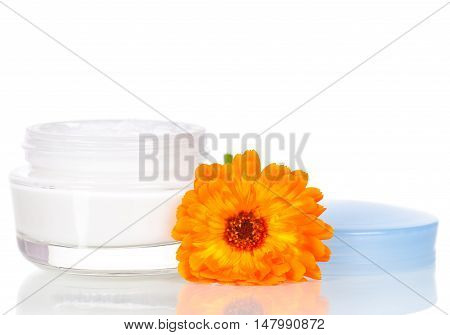 Jar of moisturizing face cream and fresh marigold flower isolated on white background