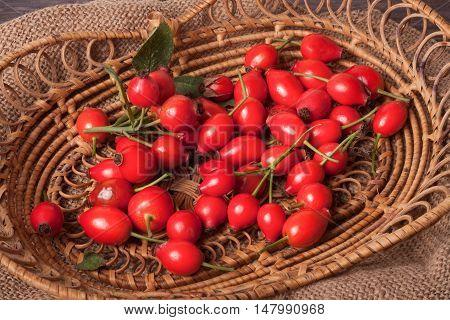 rosehips in a wicker basket on sacking.