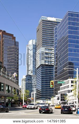 Vancouver, BC - April 20, 2015 - Vertical street scene looking up Cordova St. from Howe St. near Canada Place in the downtown heart of Vancouver on a bright sunny day. Showing modern office buildings, stores, condos, cars and people going about their day