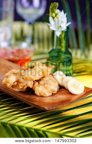 tempura bananas on a wooden plate in a tropical still life