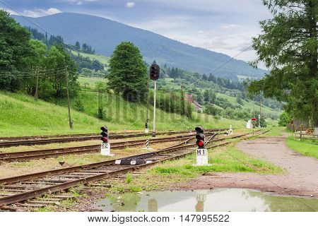 Railroad tracks and traffic lights on the railway station against the background of forested mountains in the Carpathians at summer evening