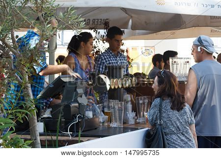 Tel Aviv Israel September 16 2016: The seller communicates with the guest of the festival at the annual beer festival in Tel Aviv Israel