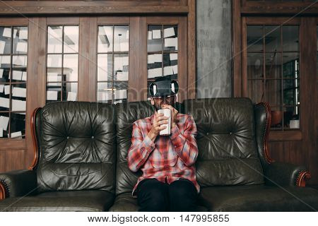 Man drinking cocktail while using vr glasses at home. Guy enjoying movie in virtual reality headset and his smoothie in ceramic glass, free space. Cinema at home, innovation, entertainment concept
