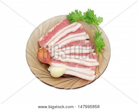 Uncooked slices of streaky pork belly bacon on glass saucer garlic cloves and sprig of cilantro on a light background