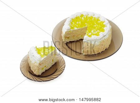 Piece of layered cake decorated with slices of lemon jelly and cut cake on a dark glass dishes on a light background