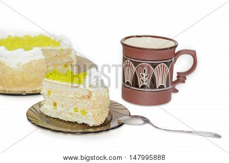 Piece of layered cake decorated with slices of lemon jelly on glass saucer and tea spoon against the background of the cup and the rest of the cake