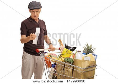 Elderly man pushing a shopping cart and looking at the bill isolated on white background