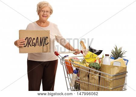 Elderly woman pushing a shopping cart and holding a cardboard sign that says organic isolated on white background