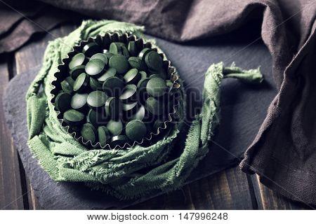 Spirulina tablets on a wooden background