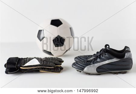 sport, soccer, football and sports equipment concept - close up of ball, boots and goalkeeper gloves