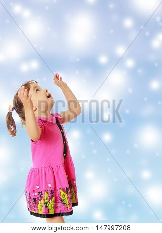 Cute little girl with pigtails on the head , in a pink dress. The girl was looking at the top turned sideways to the camera.On new year or Christmas blue background with white big stars.
