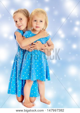 Two charming little girls, sisters , in identical blue dresses with polka dots , cuddling.On a blue background with large, white, Christmas or new year's snowflakes.