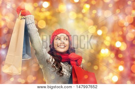 holidays, christmas, sale and people concept - happy smiling young asian woman in winter clothes with shopping bags over lights background