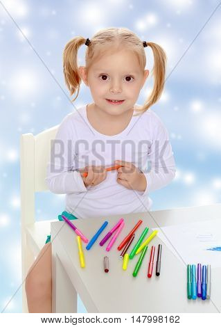 Pretty little blonde girl drawing with markers at the table.Girl holding in hands blue marker.The concept of celebrating the New year, Holy Christmas, or child's birthday on a blue background