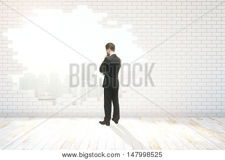 Thoughtful businessman looking out of hole with New York city view in white brick wall. 3D Rendering