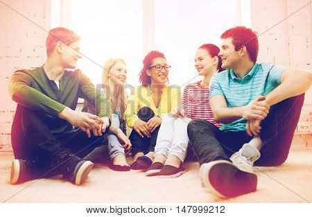 education, leisure and happiness concept - five smiling teenagers having fun at home