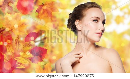 beauty, people and bodycare concept - beautiful young woman touching her neck over natural autumn leaves and lights background