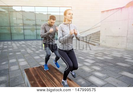 fitness, sport, training, people and lifestyle concept - couple making step exercise on city street bench