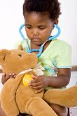 stock photo of teddy-bear  - cute african american little girl playing doctor with teddy bear - JPG