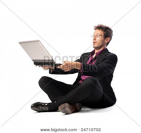 Businessman observing a laptop with astonished expression