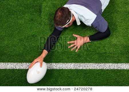 Overhead photo of a rugby player stretching over the line to score a try with one hand on the ball.