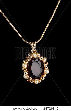 beautiful golden pendant with gem on black background