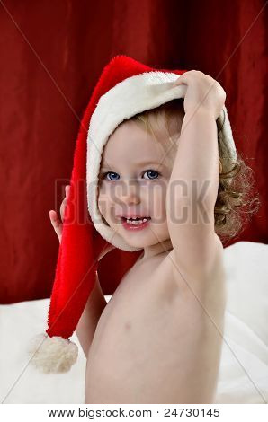 Little Girl In A Christmas Red Hat Sitting On A Bed