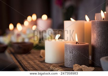 poster of Closeup of burning candles spreading aroma on table in a spa room. Beautiful composition with grey a