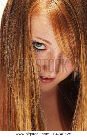 young redhead woman looking through her beautiful hair