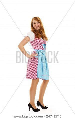 standing young redhead woman in bavarian dress
