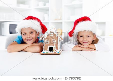 Happy kids with their gingerbread house in the kitchen at christmas time