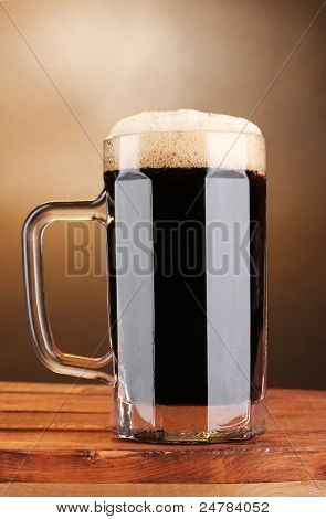 dark beer in a mug on wooden table on brown background