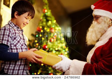 Photo of happy boy taking gift from Santa Claus hands