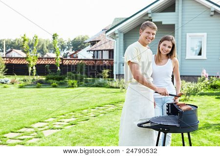 A couple with a barbecue on the lawn